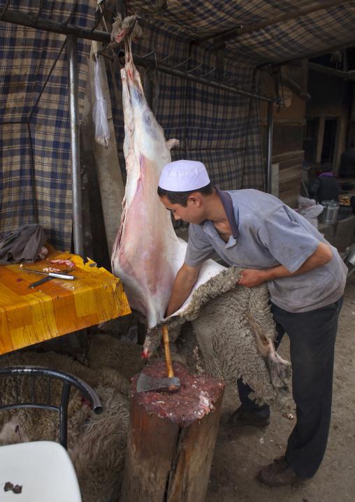 Young Uyghur Man Removing The Skin Of A Sheep, Keriya, Old Town, Xinjiang Uyghur Autonomous Region, China