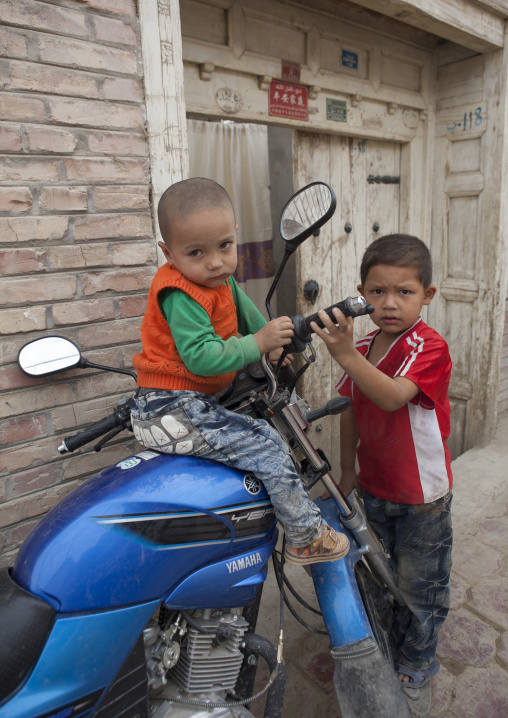 Young Uyghur Boys Playing With A Motorcycle, Keriya, Old Town, Xinjiang Uyghur Autonomous Region, China