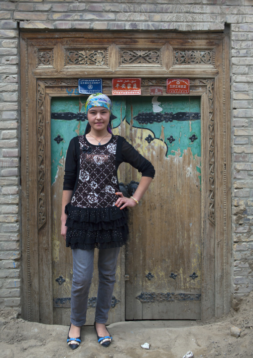 Young Uyghur Woman Posing In Front Of A Traditional Door In Old Town, Keriya, Xinjiang Uyghur Autonomous Region, China