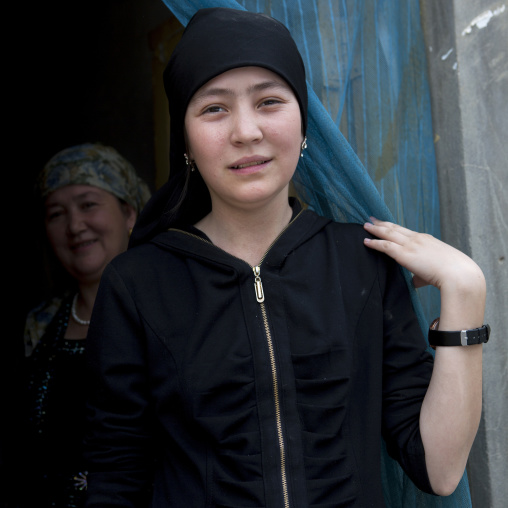 Young Uyghur Woman And Her Mother At The Entrance Of Their House, Keriya, Xinjiang Uyghur Autonomous Region, China