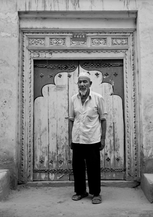 Old Uyghur Man In Front Of A Traditional Door In Old Town, Keriya, Xinjiang Uyghur Autonomous Region, China