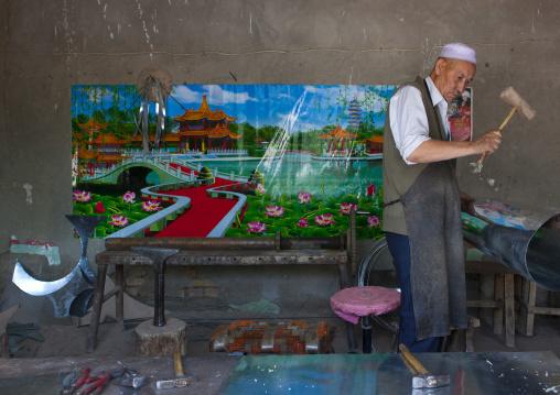 Uyghur Blacksmith Man Working, Minfeng, Xinjiang Uyghur Autonomous Region, China