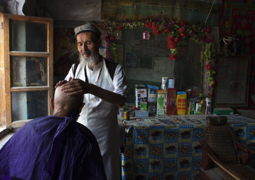 Uyghur Barber In His Shop Shaving The Head Of A Client, Minfeng, Xinjiang Uyghur Autonomous Region, China