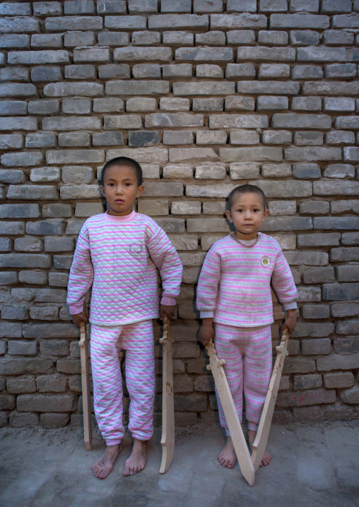 Uyghur Kids With Wooden Swords In The Street Posing Against A Brick Wall, Yarkand, Xinjiang Uyghur Autonomous Region, China
