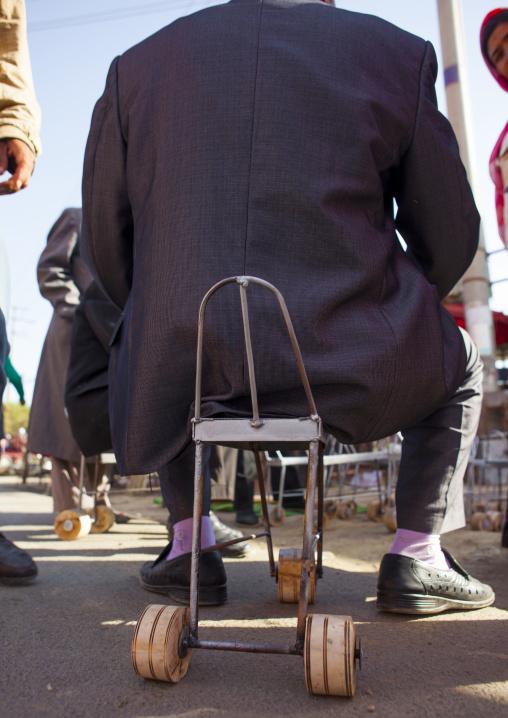 Uyghur Man Sitting On A Chair With Wheels Used To Harvest Cotton, Serik Buya Market, Yarkand, Xinjiang Uyghur Autonomous Region, China