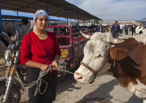 Young Uyghur Woman Showing her Cow, Serik Buya Market, Yarkand, Xinjiang Uyghur Autonomous Region, China