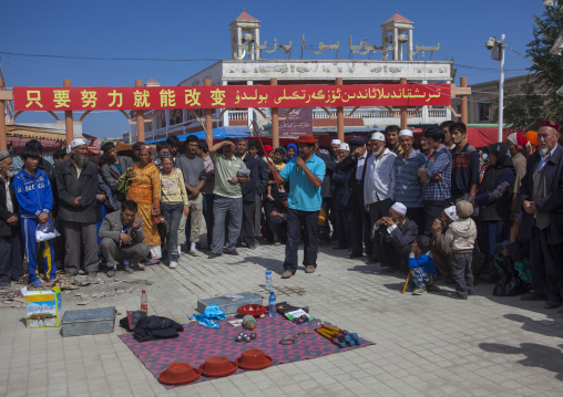 Seller making a show, Serik Buya Market, Yarkand, Xinjiang Uyghur Autonomous Region, China