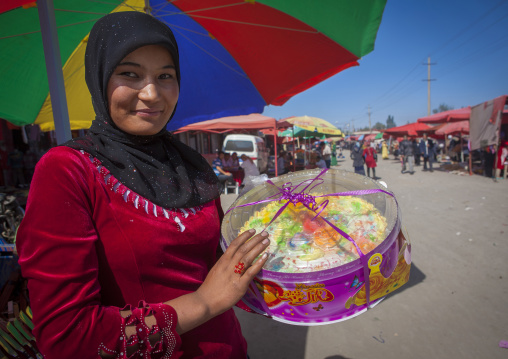 Young Uyghur Woman With big Cake, Serik Buya Market, Yarkand, Xinjiang Uyghur Autonomous Region, China