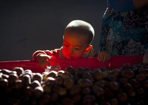 Uyghur Kid Playing Near Piles Of Dates, Kashgar,  Xinjiang Uyghur Autonomous Region, China