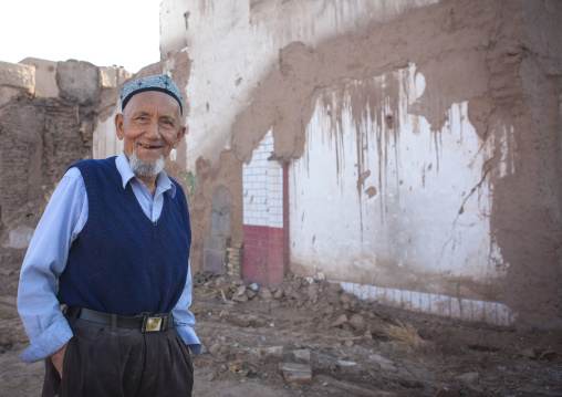 Uyghur Man In Front Of Demolished House, Old Town Of Kashgar, Xinjiang Uyghur Autonomous Region, China