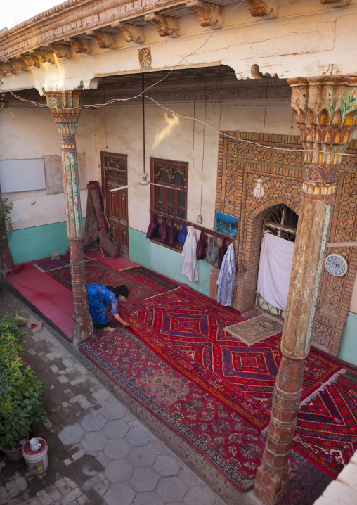 Uygur Woman Uncoiling The Carpets Of A Mosque, Old Town Of Kashgar, Xinjiang Uyghur Autonomous Region, China