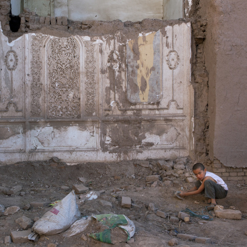 Kid In The Rubble Of A Demolished House, Old Town Of Kashgar, Xinjiang Uyghur Autonomous Region, China