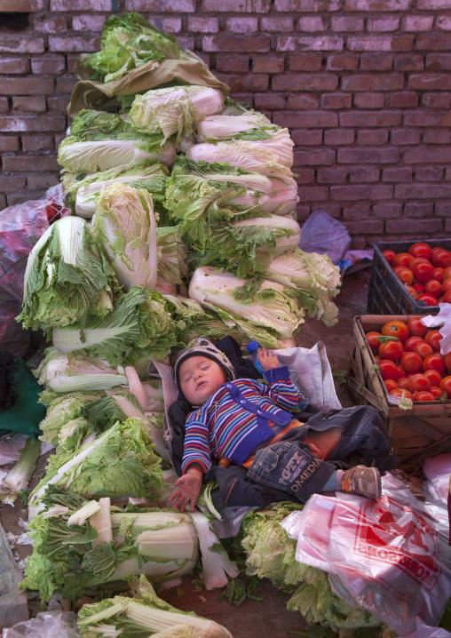 Baby Sleeping In The Vegetables, Opal Village Market, Xinjiang Uyghur Autonomous Region, China