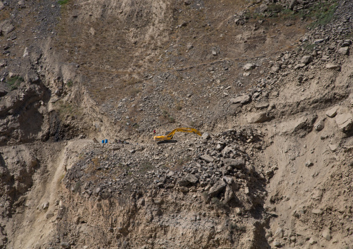 Yellow excavator working on amountain road, Badakhshan province, Darmadar, Afghanistan