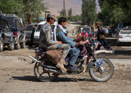 Men riding a motorcycle in the streets of the market, Badakhshan province, Ishkashim, Afghanistan