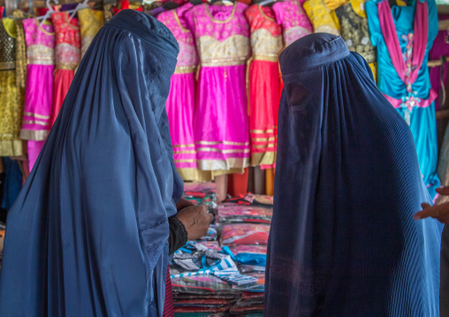 Women wearing burkas in the market byuing clothes, Badakhshan province, Ishkashim, Afghanistan