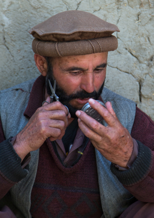 Afghan man cutting his beard in the street, Badakhshan province, Ishkashim, Afghanistan