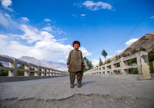 Afghan boy standing in the middle of a bridge, Badakhshan province, Khandood, Afghanistan