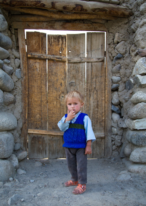 Afghan boy with blonde hair in front of a wooden door, Badakhshan province, Khandood, Afghanistan