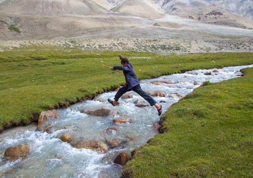 Wakhi boy jumping over a river in pamir mountains, Big pamir, Wakhan, Afghanistan
