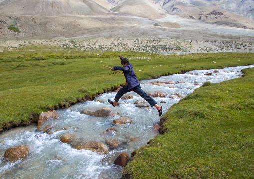 Wakhi boy jumping over a river in pamir mountains, Big pamir, Wakhan, Afghanistan