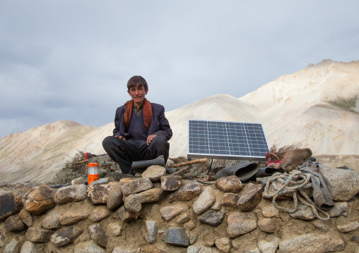 Wakhi nomad teenager sitting near a solar panel, Big pamir, Wakhan, Afghanistan