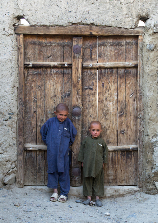 Afghan boys with shaved heads standing in front of a wooden door, Badakhshan province, Khandood, Afghanistan