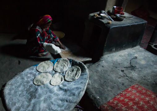 Afghan woman making bread inside her traditional pamiri house, Badakhshan province, Khandood, Afghanistan