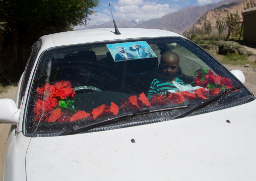 Afghan boy inside a car with ahmad shah massoud poster on the windshield, Badakhshan province, Khandood, Afghanistan