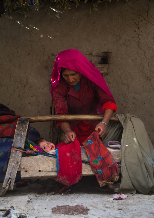 Mother looking after her baby in a craddle, Badakhshan province, Qazi deh, Afghanistan