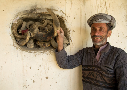 Afghan man showing the ibex horns used during ramadan and nowruz celebrations, Badakhshan province, Zebak, Afghanistan