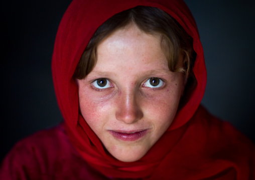 Portrait of an afghan girl with pale skin wearing red clothes, Badakhshan province, Khandood, Afghanistan