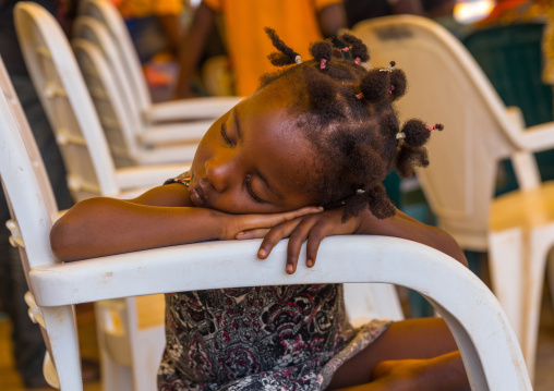 Benin, West Africa, Porto-Novo, little girl sleeping on a chair arm