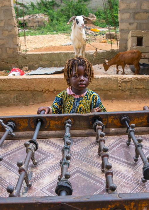 Benin, West Africa, Porto-Novo, girl plays table football babyfoot in the street