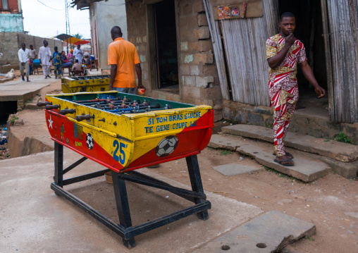 Benin, West Africa, Porto-Novo, men passing in front of a table football babyfoot in the street