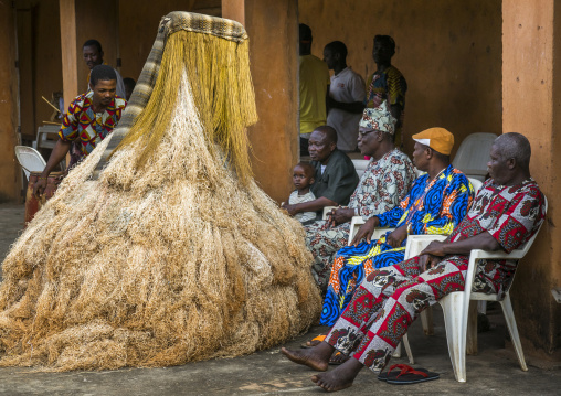 Benin, West Africa, Porto-Novo, men speaking to a zangbeto guardian of the night spirit in the royal palace