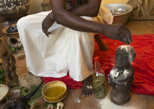 Benin, West Africa, Bonhicon, kagbanon bebe voodoo priest putting some talc on the head of a statue during a ceremony