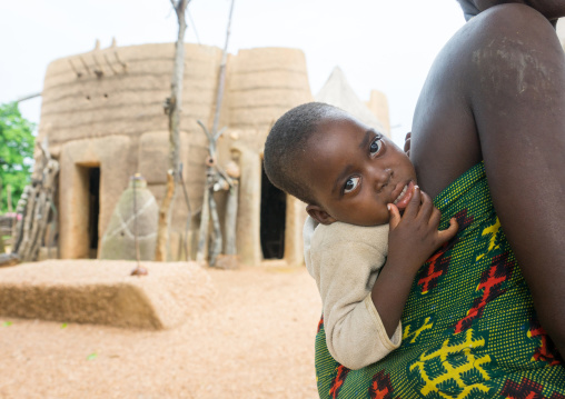 Benin, West Africa, Boukoumbé, baby in front of a traditional tata somba house
