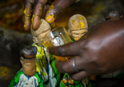 Benin, West Africa, Bopa, miss ablossi giving drink to the carved wooden figures of her five dead twins