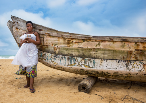 Benin, West Africa, Ouidah, mrs kpsouayo carrying the carved wooden figures made to house the soul of her dead twins