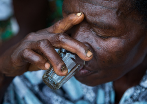 Benin, West Africa, Bopa, woman drinking alcohol during a voodoo ceremony