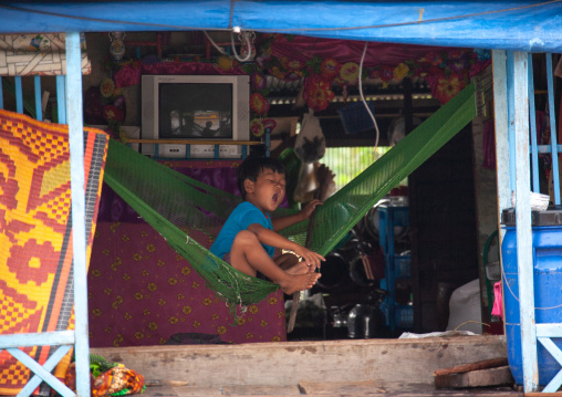 Cambodian boy on a hammock in the floating village on Tonle Sap lake, Siem Reap Province, Chong Kneas, Cambodia