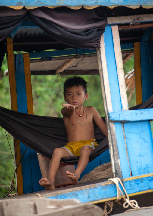 Cambodian boy on a hammock asking for money in the floating village on Tonle Sap lake, Siem Reap Province, Chong Kneas, Cambodia