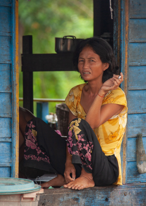 Cambodian woman sit at the door of her house in the floating village on Tonle Sap lake, Siem Reap Province, Chong Kneas, Cambodia