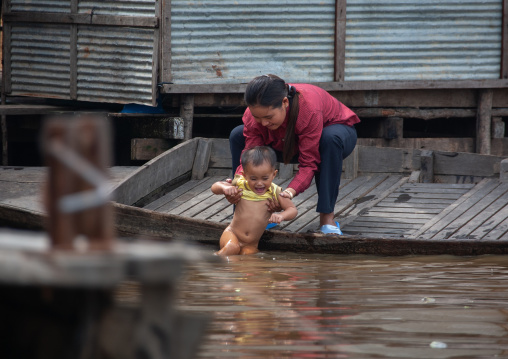 Cambodian mother giving a bath in Tonle Sap lake, Siem Reap Province, Chong Kneas, Cambodia
