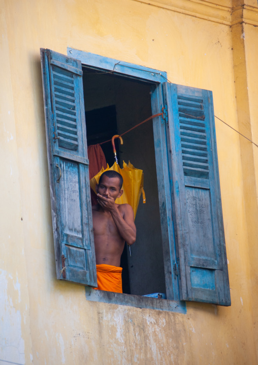 Cambodian monk standing at the window in a monastery, Battambang province, Battambang, Cambodia
