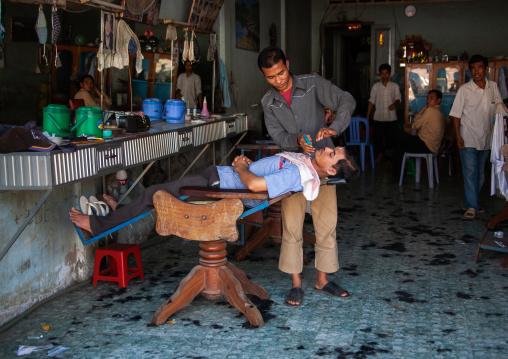 Men having their hair cut in a salon, Battambang province, Battambang, Cambodia
