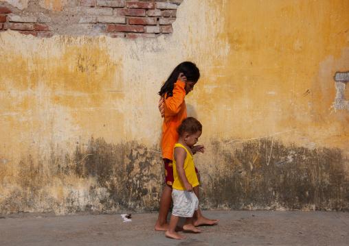Two children holding hands and walking along a wall, Battambang province, Battambang, Cambodia