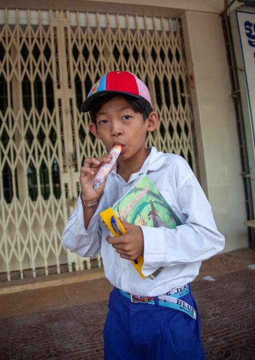 Portrait of boy eating ice cream while standing on street, Battambang province, Battambang, Cambodia