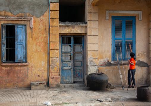 Cambodian woman closing the windows of an old colonial house, Battambang province, Battambang, Cambodia